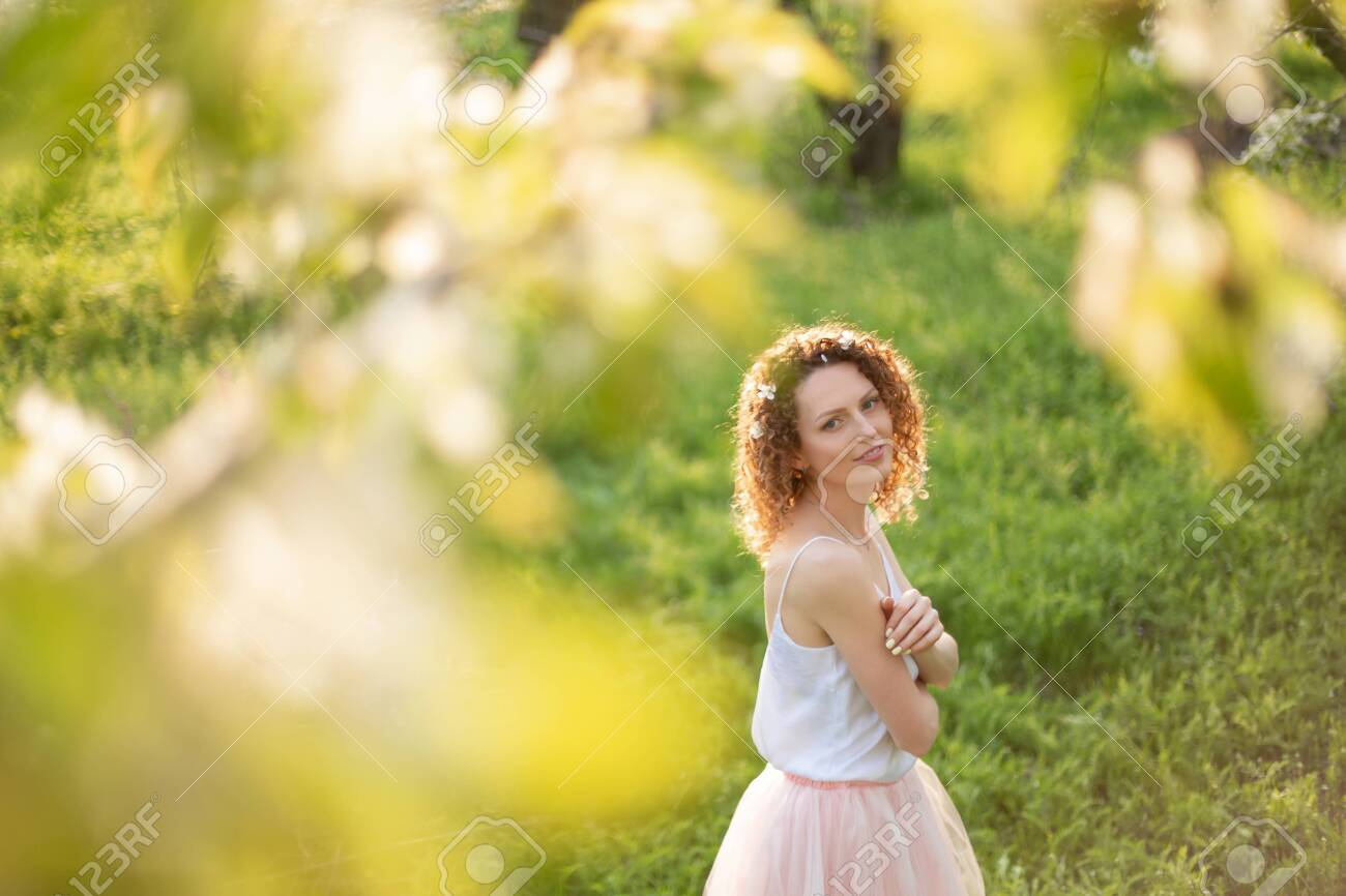 Young attractive girl walks in spring green park enjoying flowering nature. Healthy smiling girl spinning on the spring lawn. Allergy without. - 138420757
