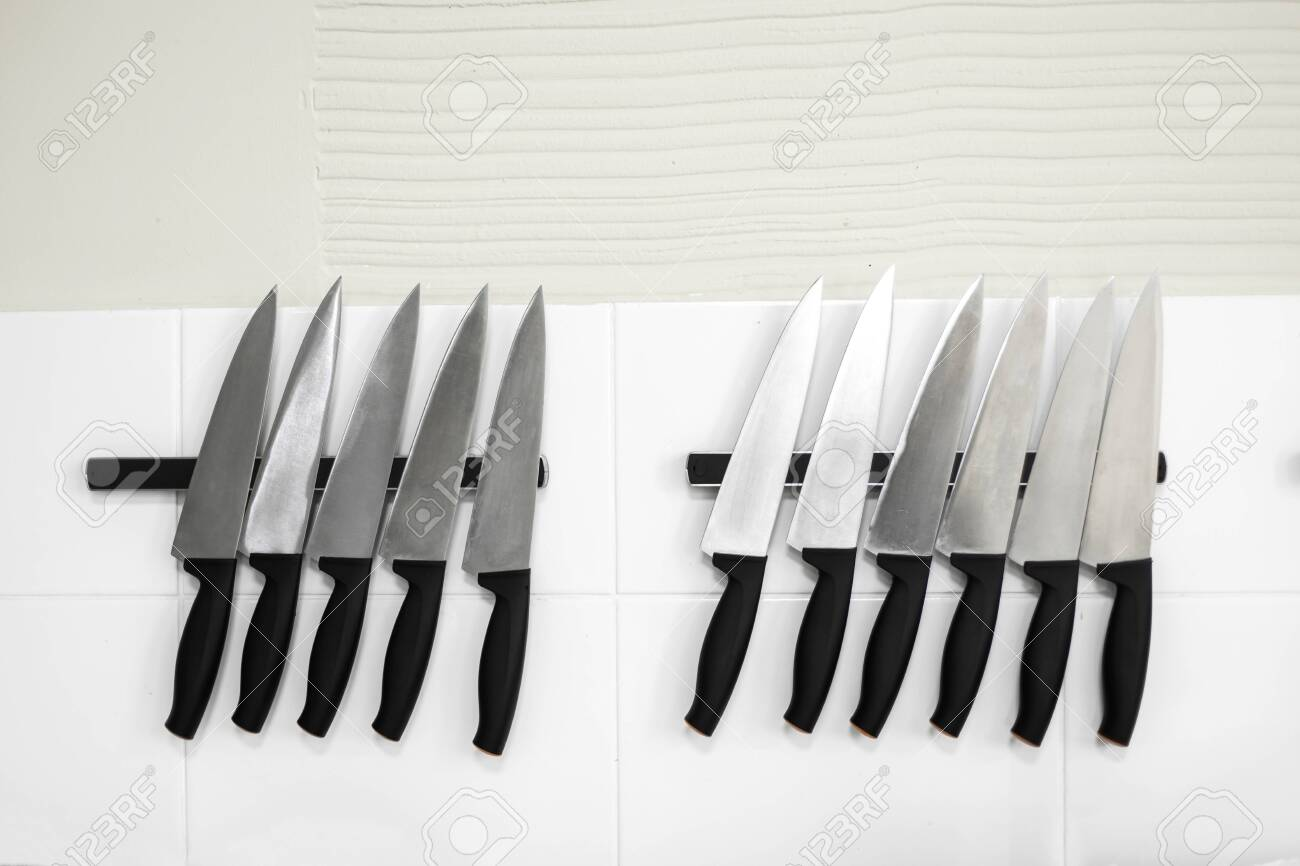 Set Of Kitchen Knives On Magnetic Tapes In The Kitchen Stock