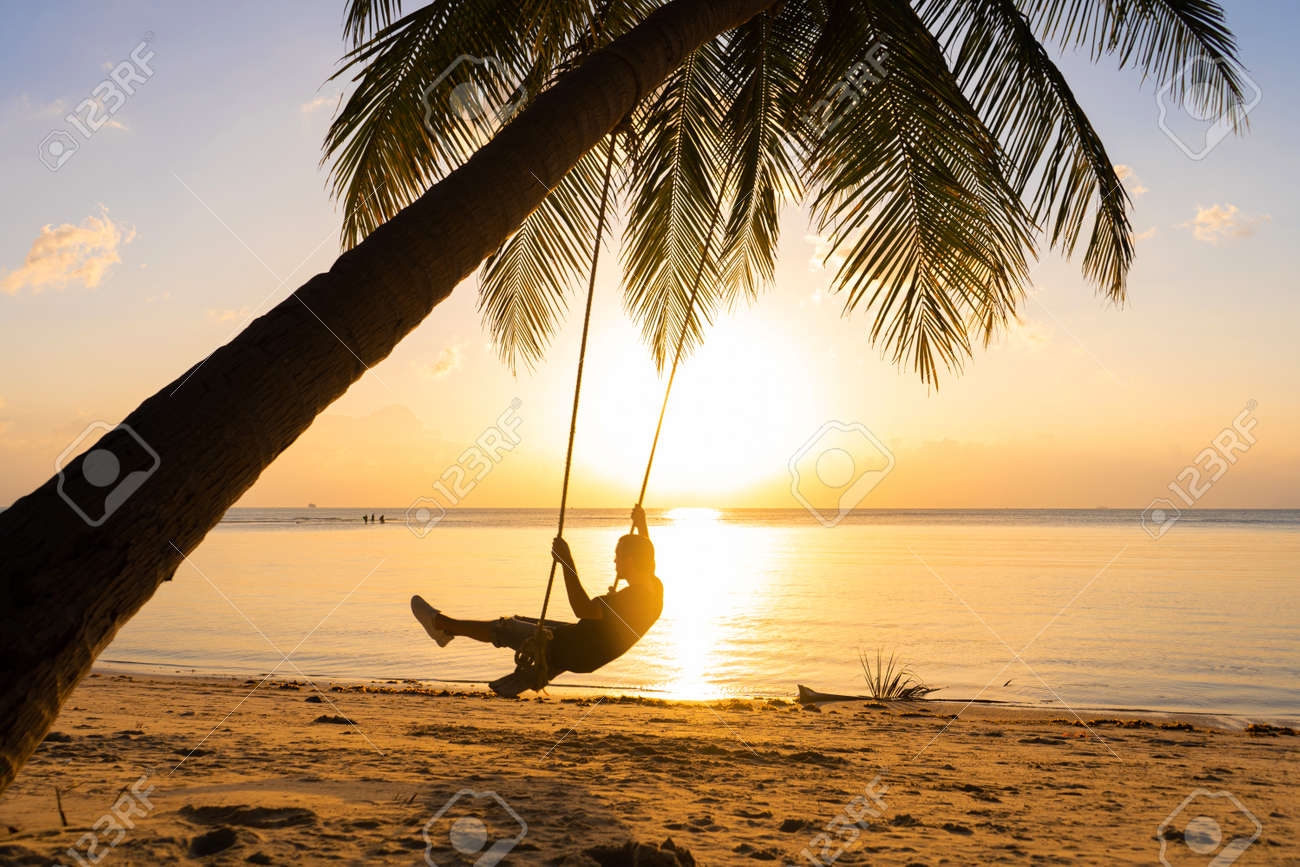 The guy enjoys the sunset riding on a swing on the ptropical beach. Silhouettes of a guy on a swing hanging on a palm tree, watching the sunset in the water - 146474754