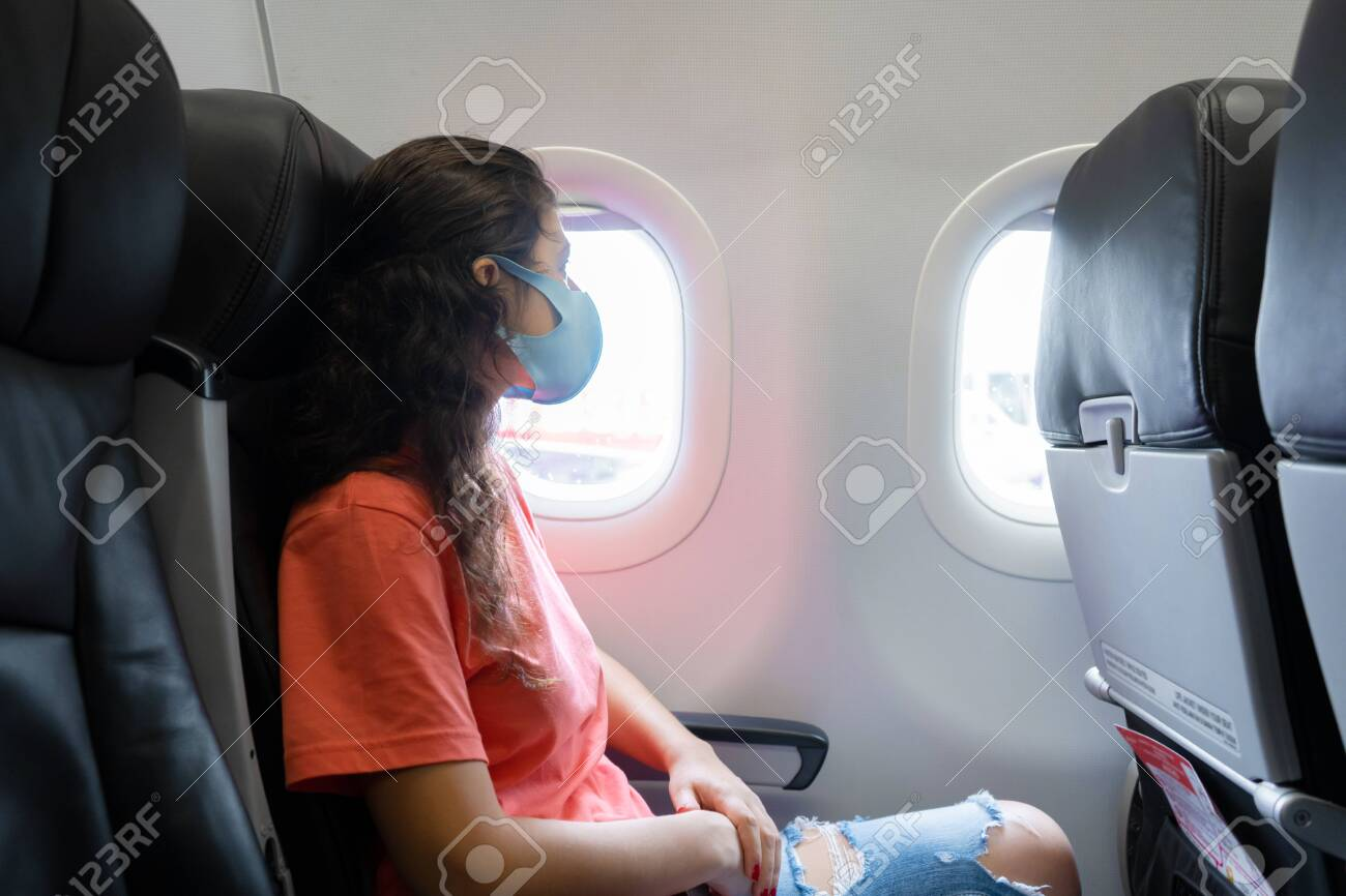 A girl in a medical mask on her face during a flight in the cabin. Air travel during a pandemic. - 153161973