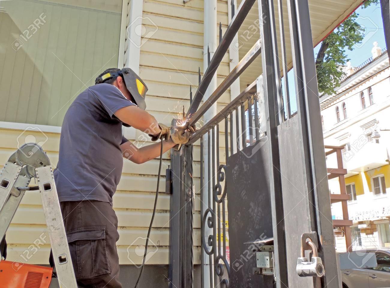 trabajador con una careta y guantes de pie en la puerta de metal de soldadura escalera
