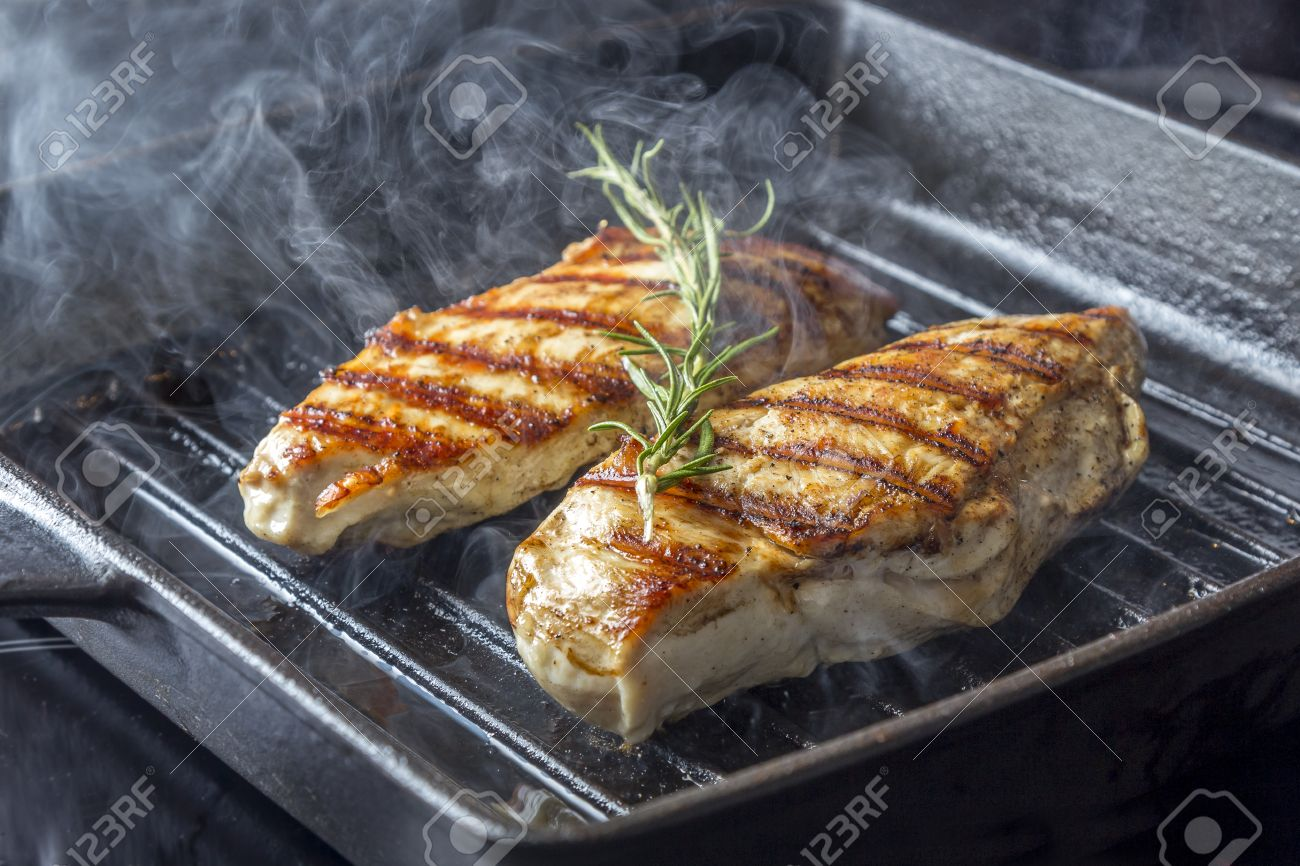 Stock Photo  Two Golden Fried Pieces Of Chicken Breast In A Griddle Pan  With Rosemary