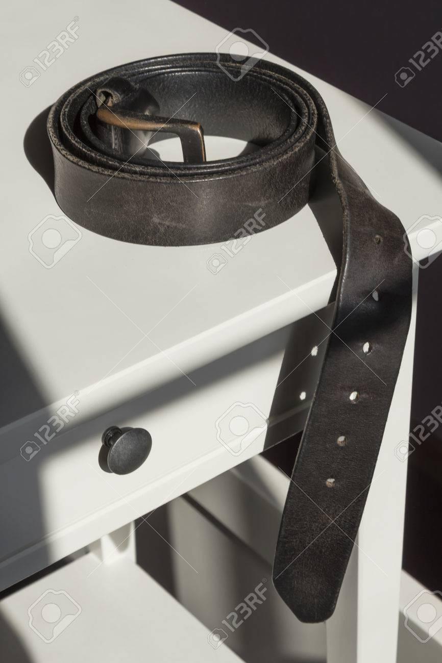 Enroule Cuir Noir Mens Ceinture Sur Une Table De Chevet Blanc Banque