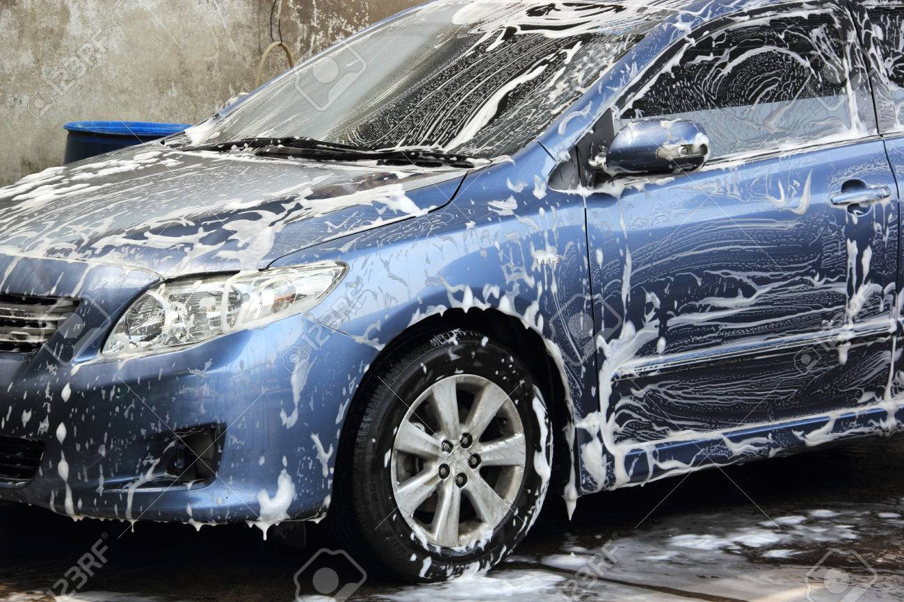 washing a blue car with a foam and water Stock Photo - 24128908