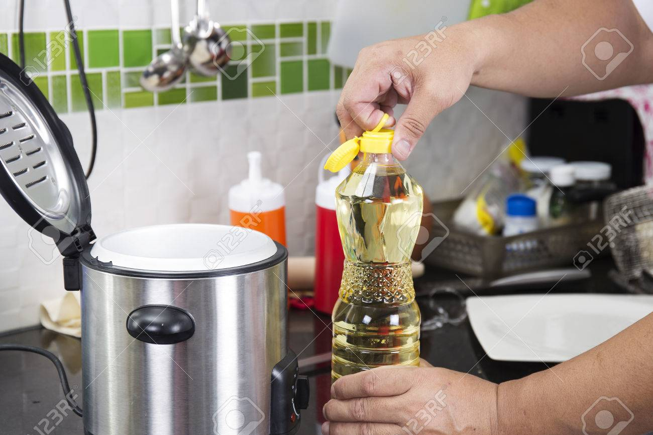 Chef open cap of vegetable oil bottle before cooking