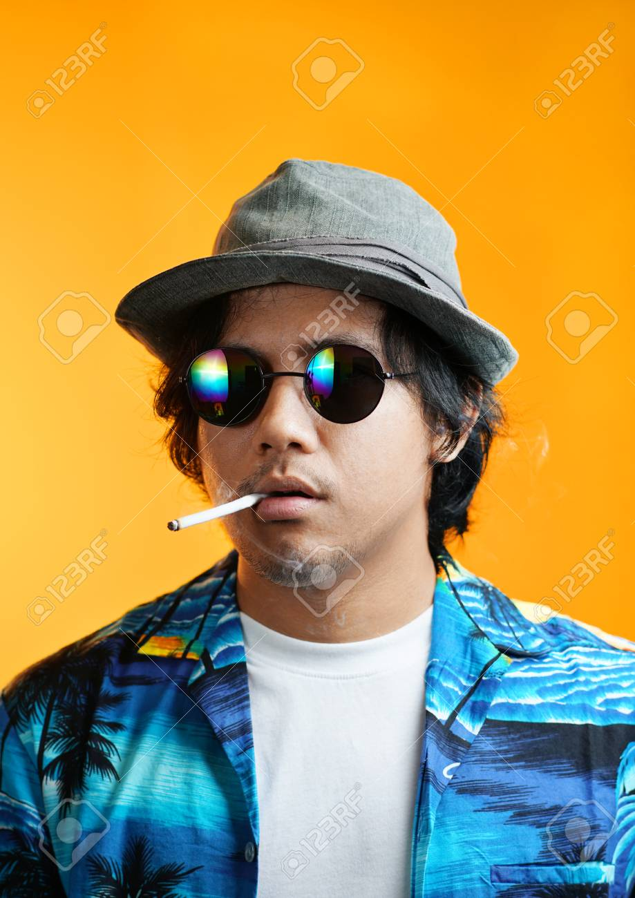 Hawaiian Gangster Smoking a Cigarette Wearing Fedora Hat and Sunglasses  against Yellow Background Stock Photo - a3f6f9e87ce