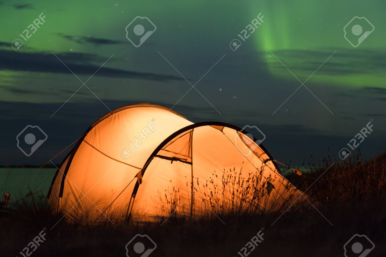 Northern lights dancing over an iluminated tent at the Atlantic coast in Norway - 81938553