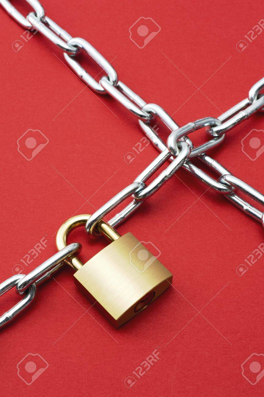 Padlock with chain on red background Stock Photo - 16277629