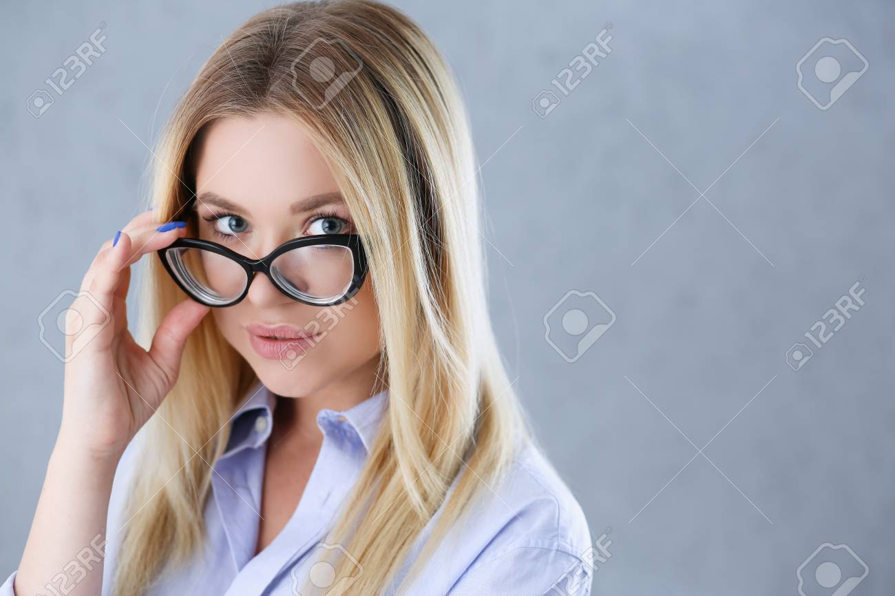 15326779401 Portrait of a sexy woman in a man's shirt wearing glasses on a gray  background looks