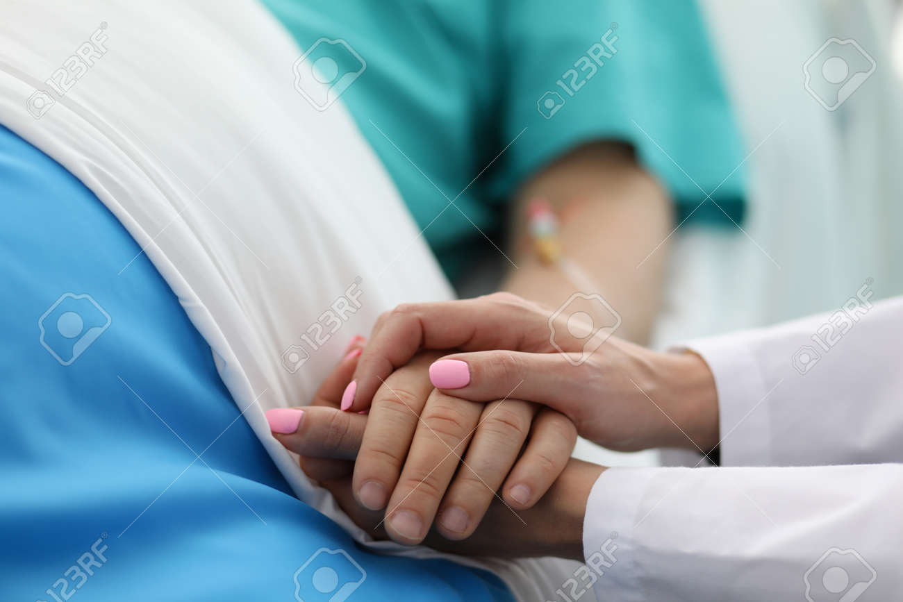 Close-up of people holding hands of each other. Woman calming to sick patient in hospital ward. Doc asking about well-being of sick person. Healthcare and medicine concept - 134193403