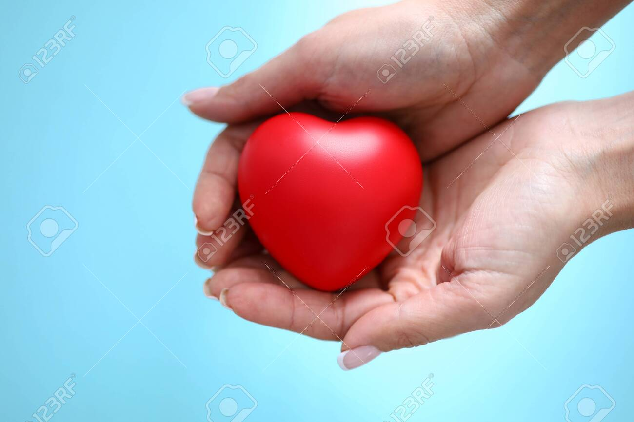 Woman hand hold red toy heart in hand against blue background closeup. Charity people concept - 136885315