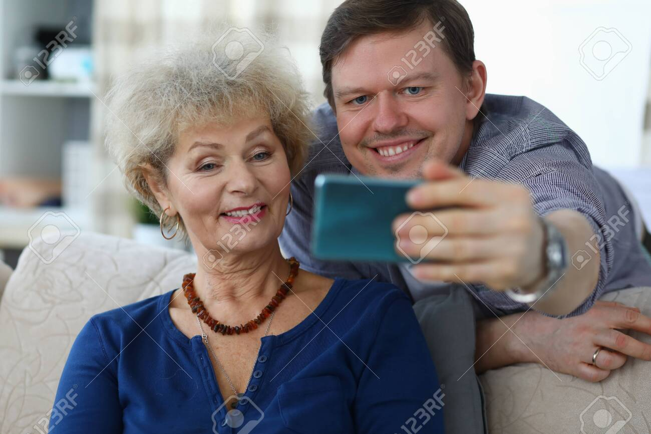 Portrait of cheerful mother and son taking selfie to remember. Smiling elderly woman posing for picture on sofa at home. Family relationship and spare time concept - 143029190