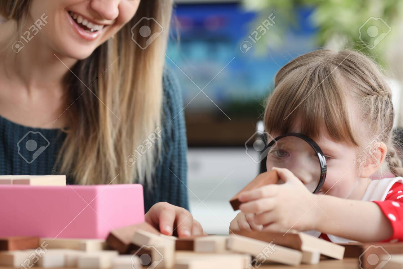 Daughter looks through magnifier at wooden bar. Girl learns to think strategically. Popular game among children and adults. Board game for development intelligence. Assemble tower, pull blocks out it - 144867033