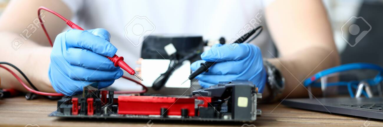 Close-up of male wearing protective blue gloves and using voltmeter on repairing detail. Middle-aged man measuring voltage. Technology and diy concept - 149848508