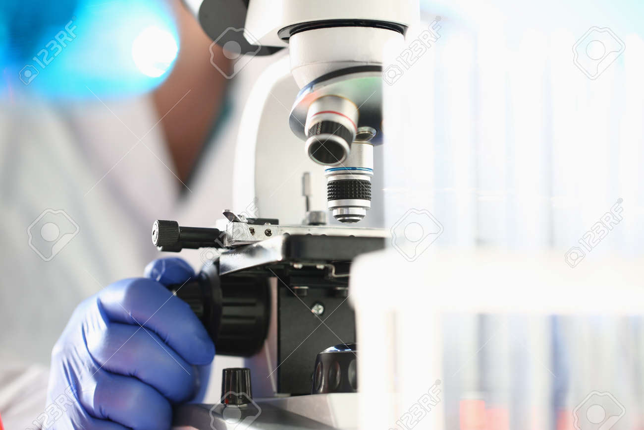 Close up of male researcher in sterile gloves looking at biological samples under microscope - 150074206