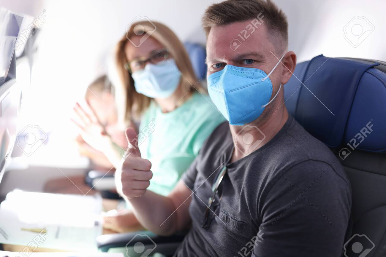 Husband and wife are flying on plane wearing medical masks. Sanitary standards of flight during epidemic of coronavirus infection concept. - 155437737