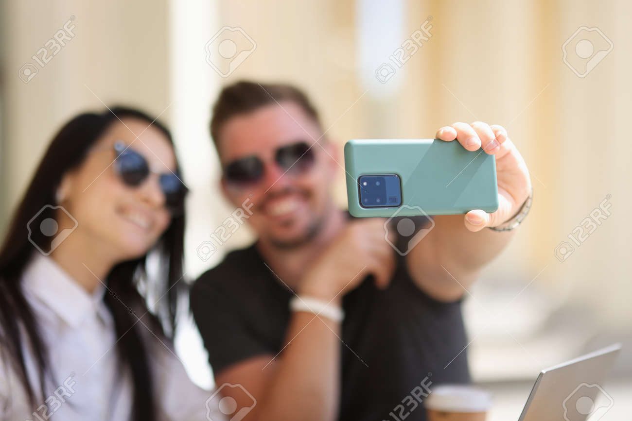 Couple take photo of themselves on phone. Man hold green phone and take photo closeup. - 155437769