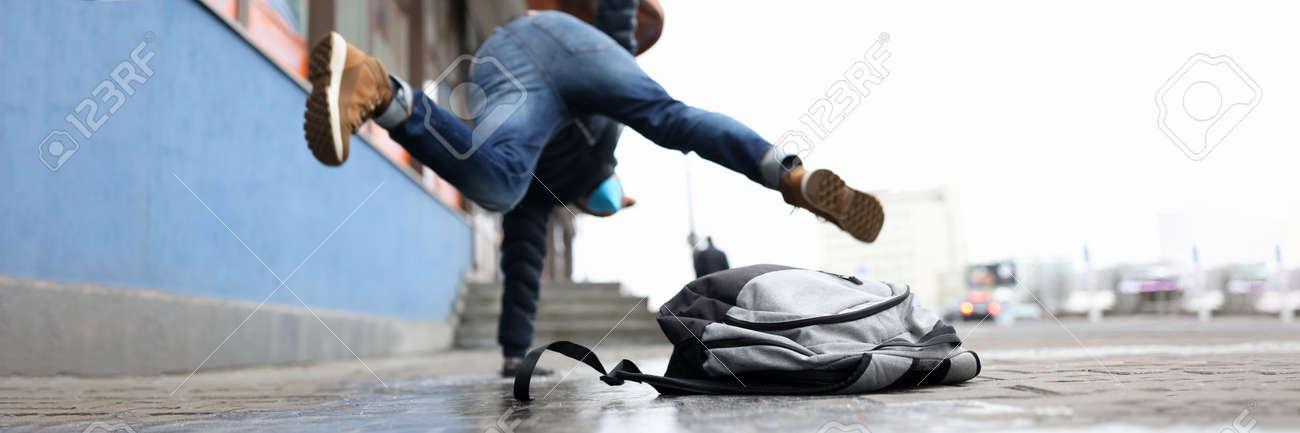 Man in winter dress slip on sidewalk with ice closeup background. Heath insurance concept - 164810852