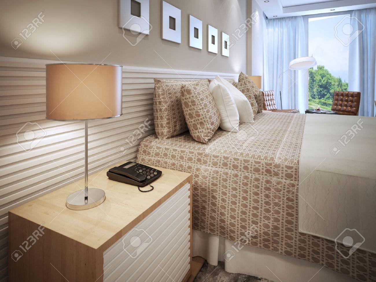Chambre design contemporain. Effectué lit avec des coussins, table de  chevet en bois avec téléphone et lampe de table avec abat-jour brun. Mur  décoré ...
