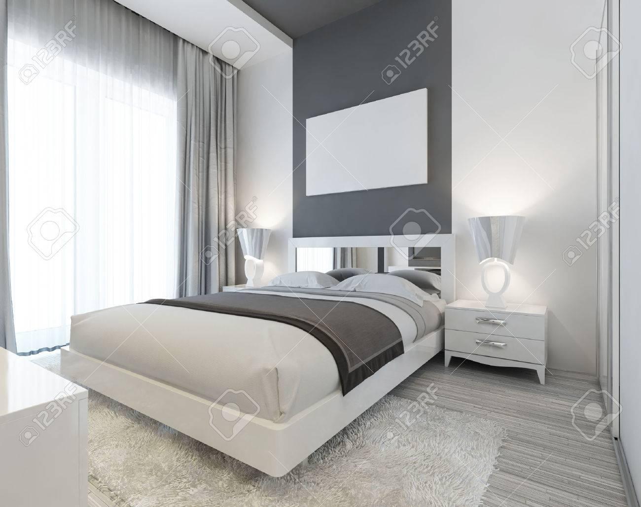 Chambre dans le style Art déco dans des couleurs blanches et grises.  Moderne soigneusement le lit posé avec des tables de chevet et lampes de  chevet.