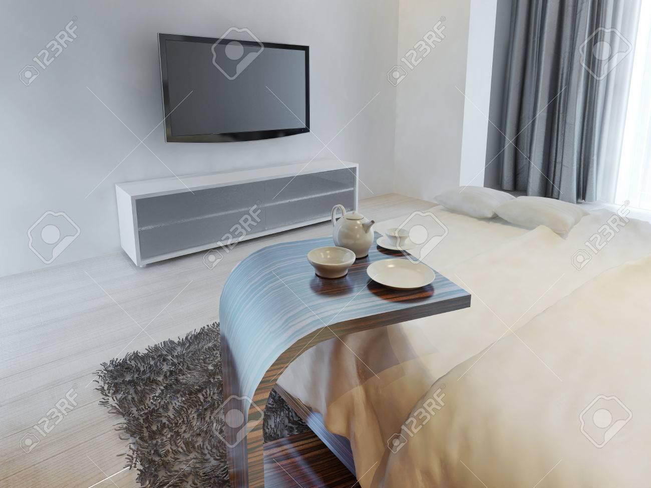 Tavolino laterale accanto al letto in stile contemporaneo con servizio di  caffè. Camera da letto con console tv in colore bianco. 3D render.