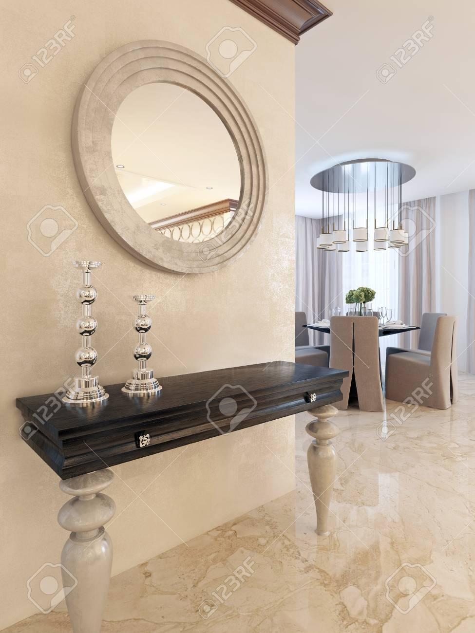 Consola con espejo en la pared en el comedor, en el estilo del Art Deco.  consola de diseño con encimera de color negro brillante y patas blancas. ...