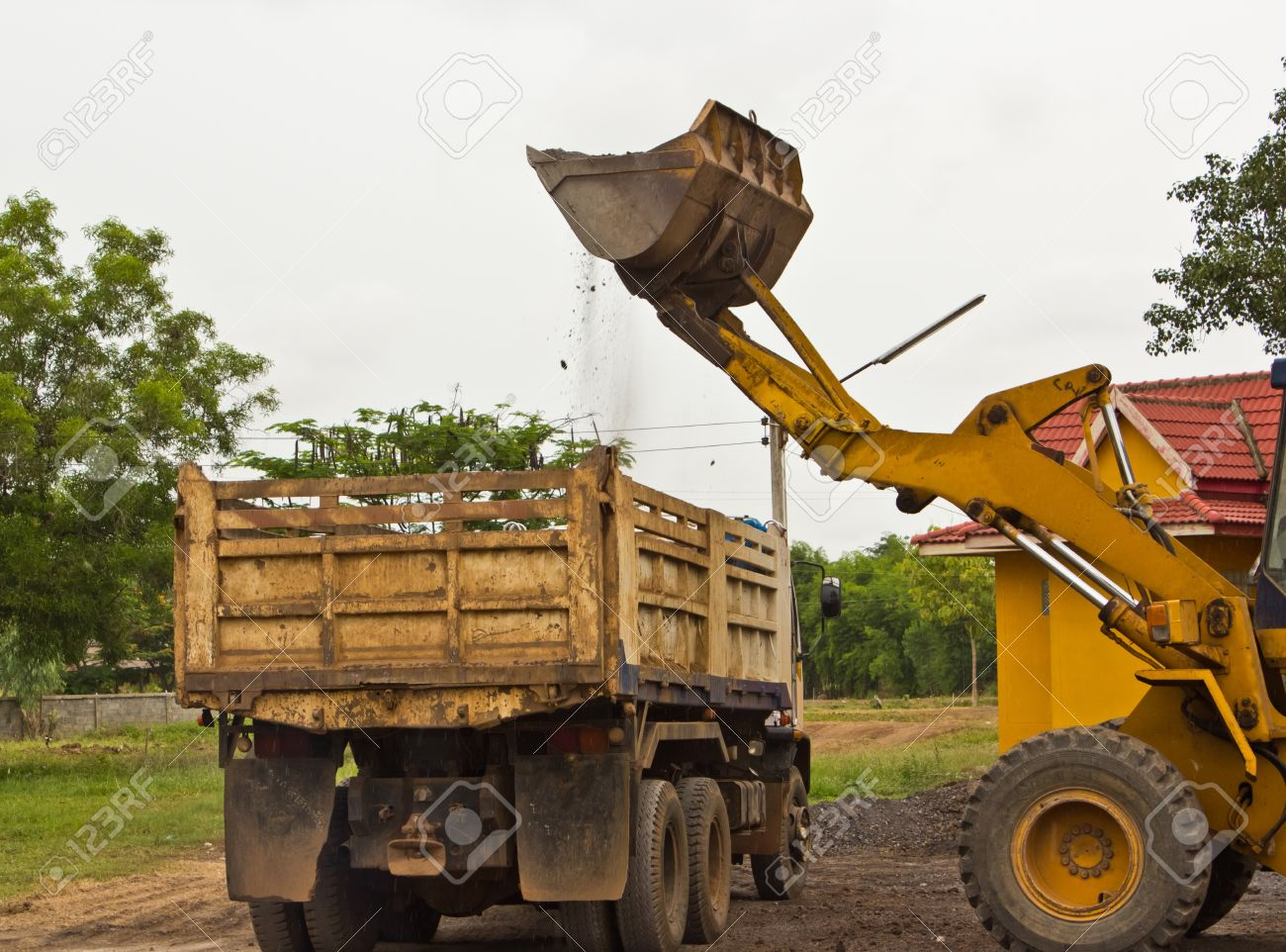 Yellow bulldozer was scooping soil into the truck  in bad weather. Stock Photo - 14250500