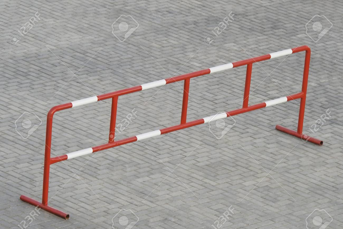 Metal barrier standing on the grey stone block paving Stock Photo - 4661351
