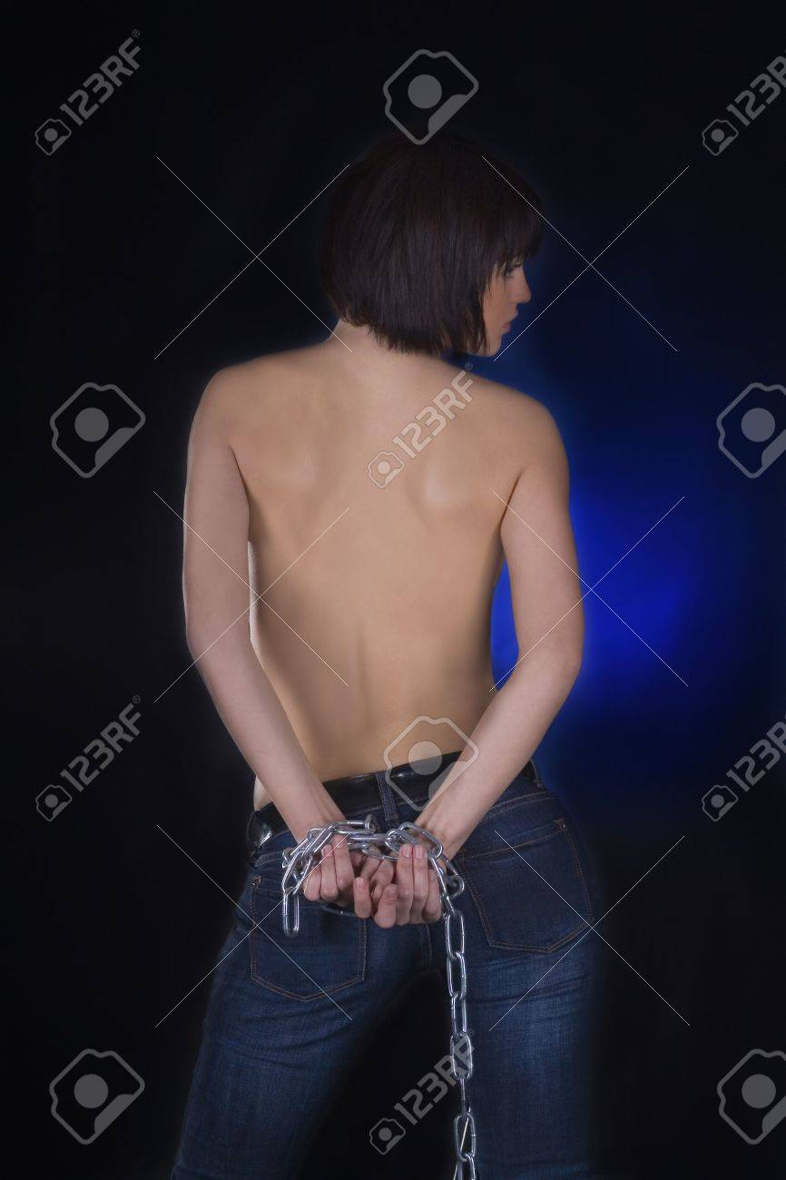 Sexy brunette with nude back in chains over black background Stock Photo - 6861291