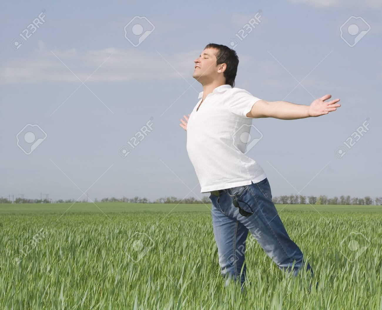 young man moves in a green field of grass Stock Photo - 7347993