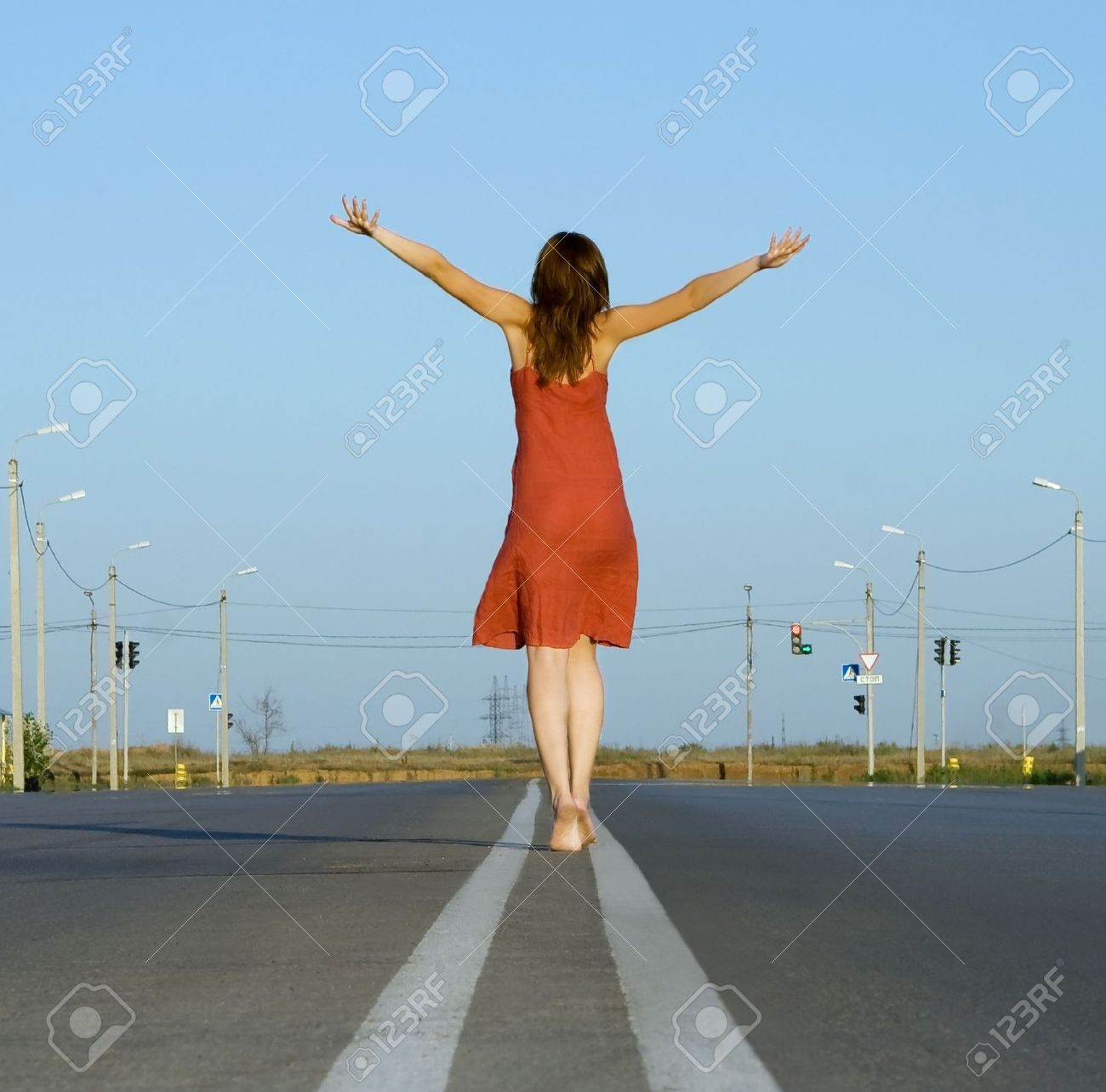 girl in red dress walk barefoot on empty road Stock Photo - 7519558