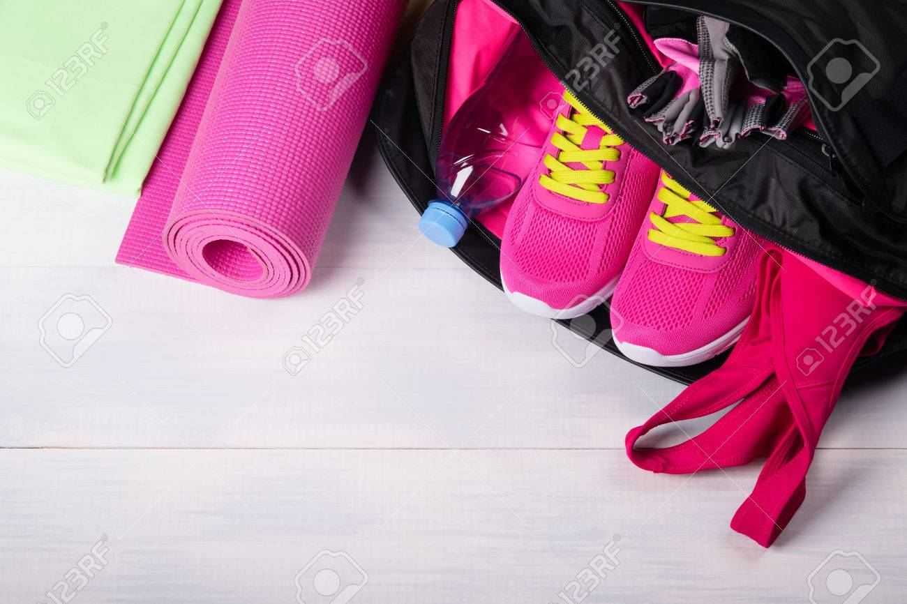 On a wooden floor a sports bag with pink things in it is opened - 83402855