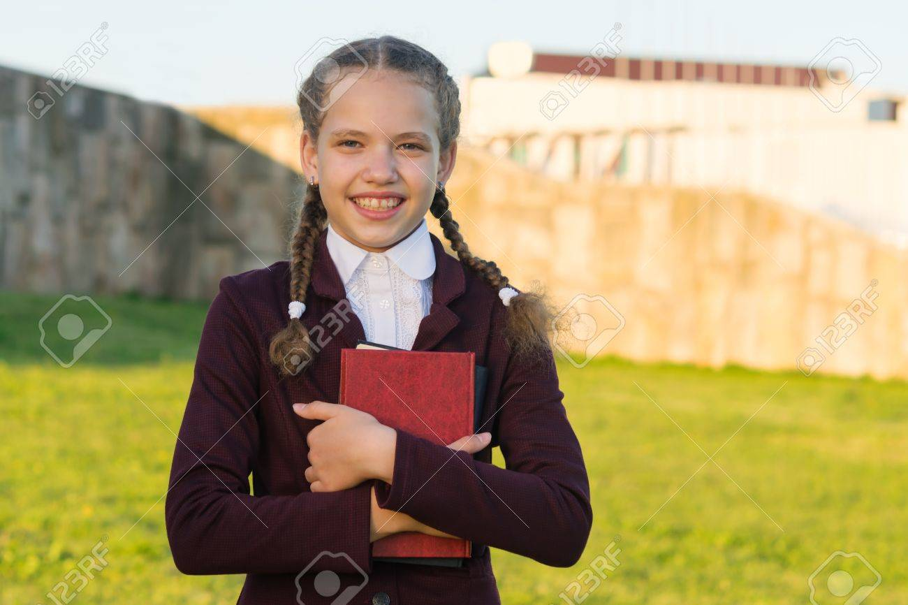 Girl in school uniform with a folder in her hands - 84549145