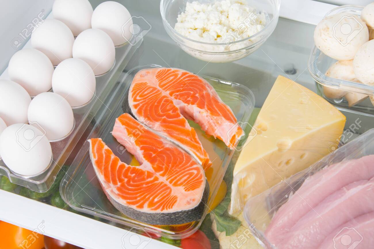 close-up shelf in the fridge where red fish, eggs, cheese, cottage cheese, mushrooms and meat - 128397857