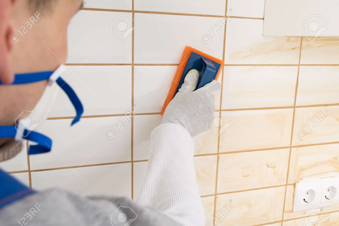 the master rubs the brown grout on white tiles with a special sponge, finishing work - 169144062