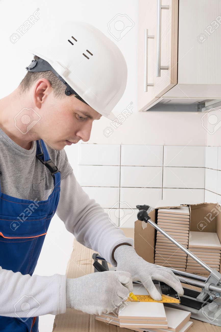 the master makes markings on ceramic white tiles for cutting, finishing work - 169144065