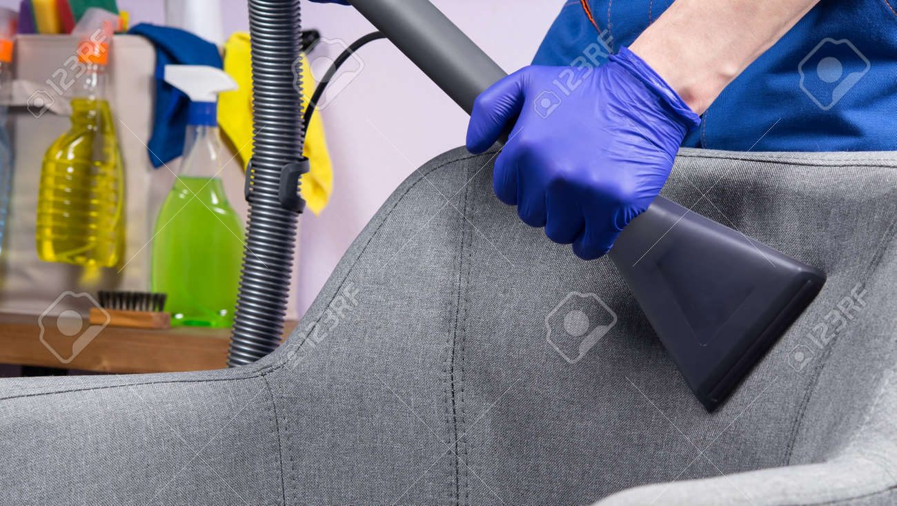 professional wet cleaning with the hands of a specialist, draping the gray fabric of the chair with a vacuum cleaner, close-up - 169657060