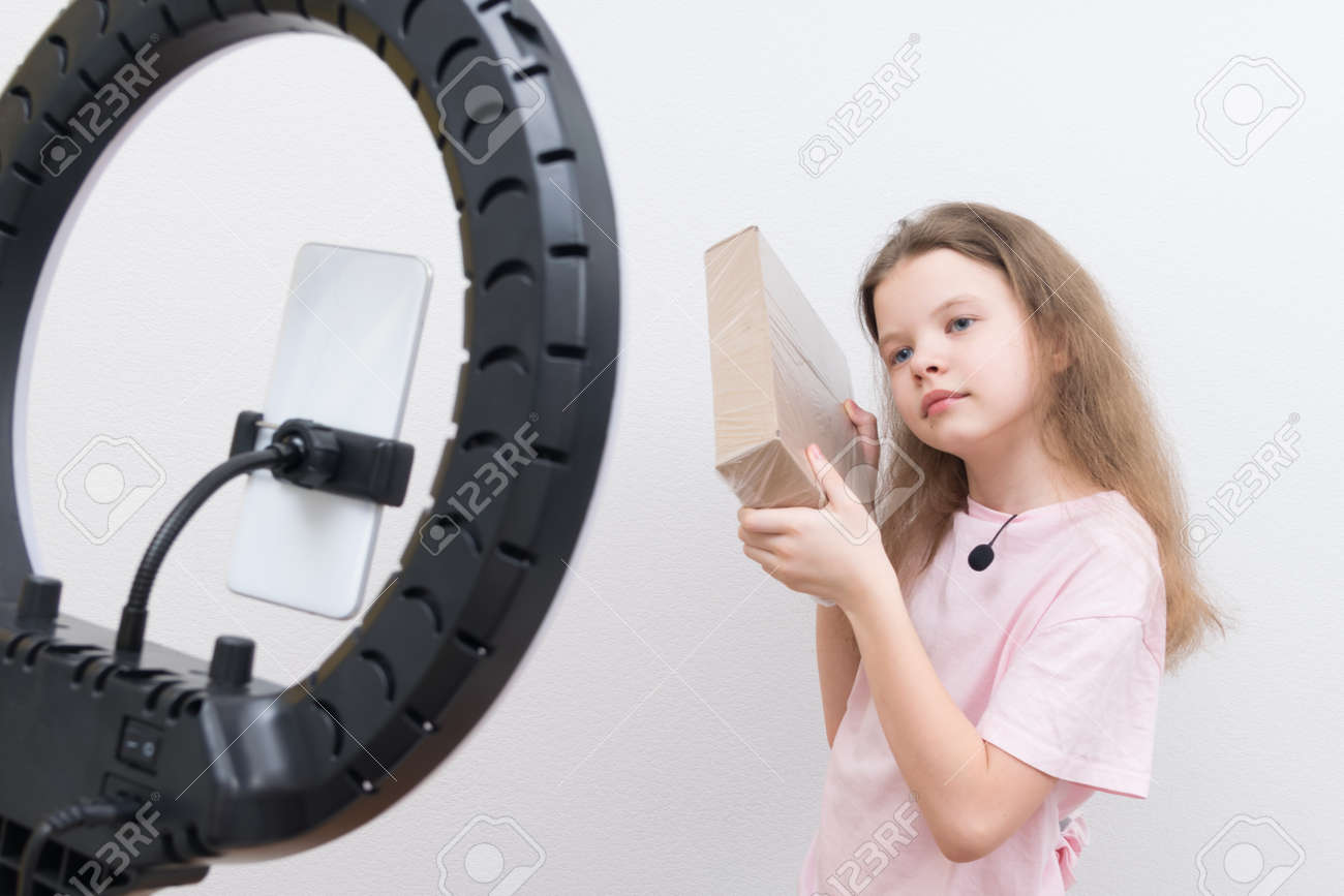 a girl blogger, in front of a circular lamp and a smartphone, makes a review of the package for unpacking - 169657127