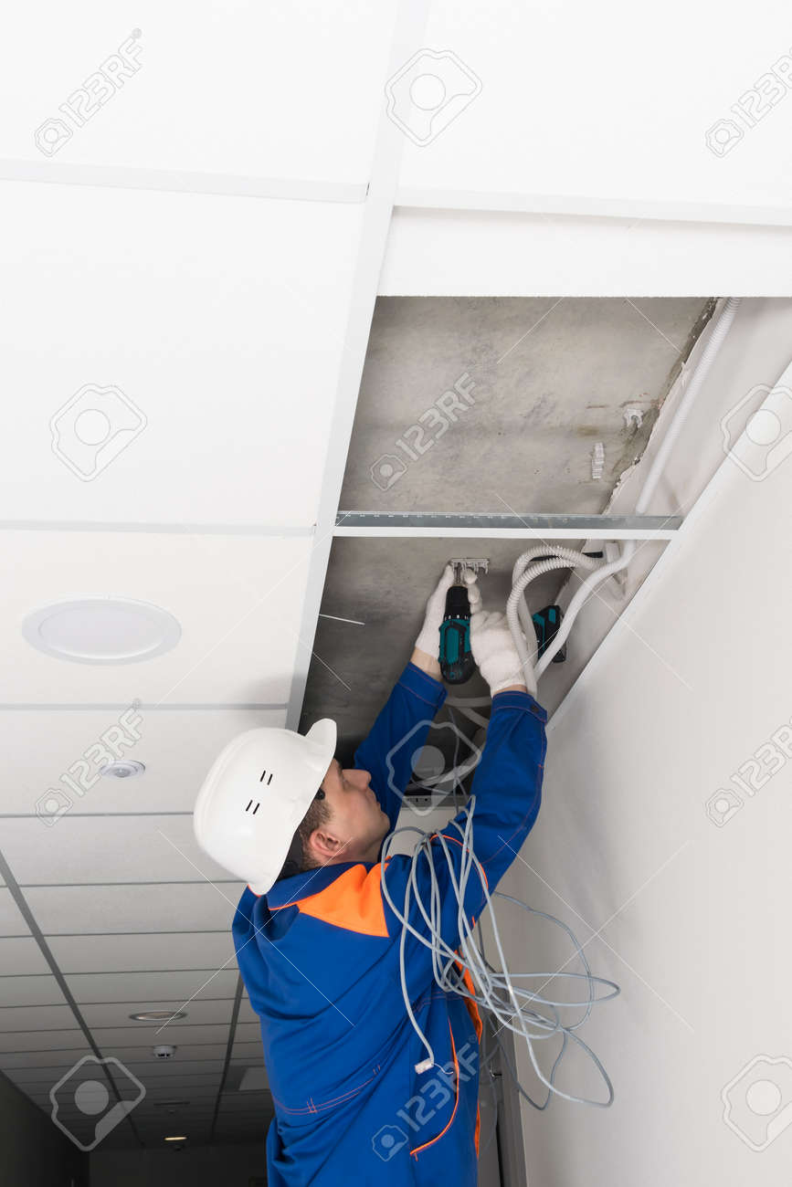 a worker screws the wire holders to the ceiling - 170101859