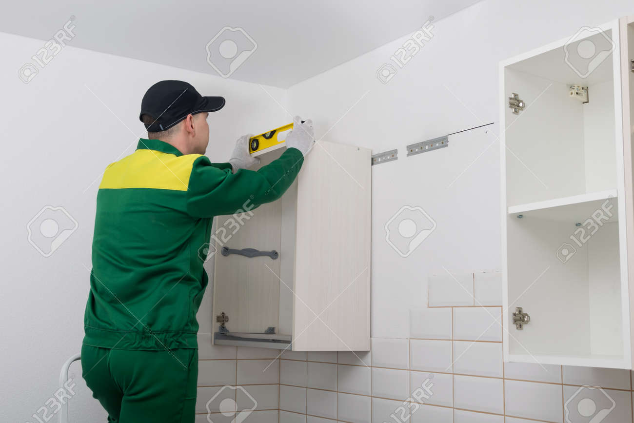 a worker checks the evenness of the installation of the upper cabinet of the kitchen set - 170101778