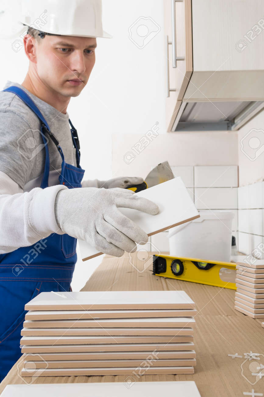 a worker takes a tile from a pile for laying it on the wall, finishing work in an apartment - 170101629