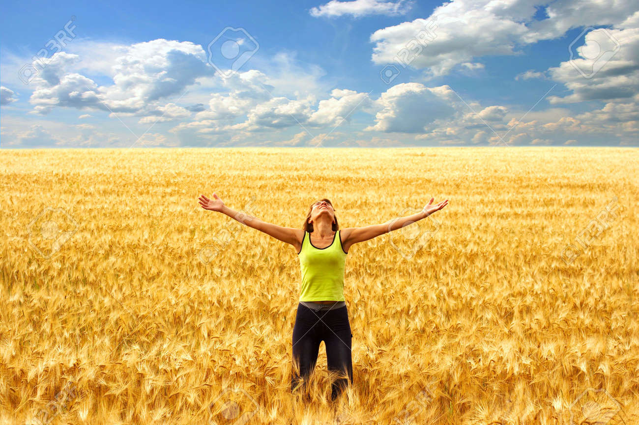 Happy young woman in the yellow field under blue sky Stock Photo - 700458
