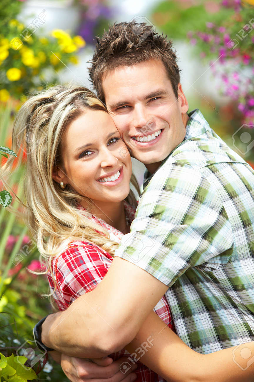 Young love couple smiling among lots of flowers Stock Photo - 3531422