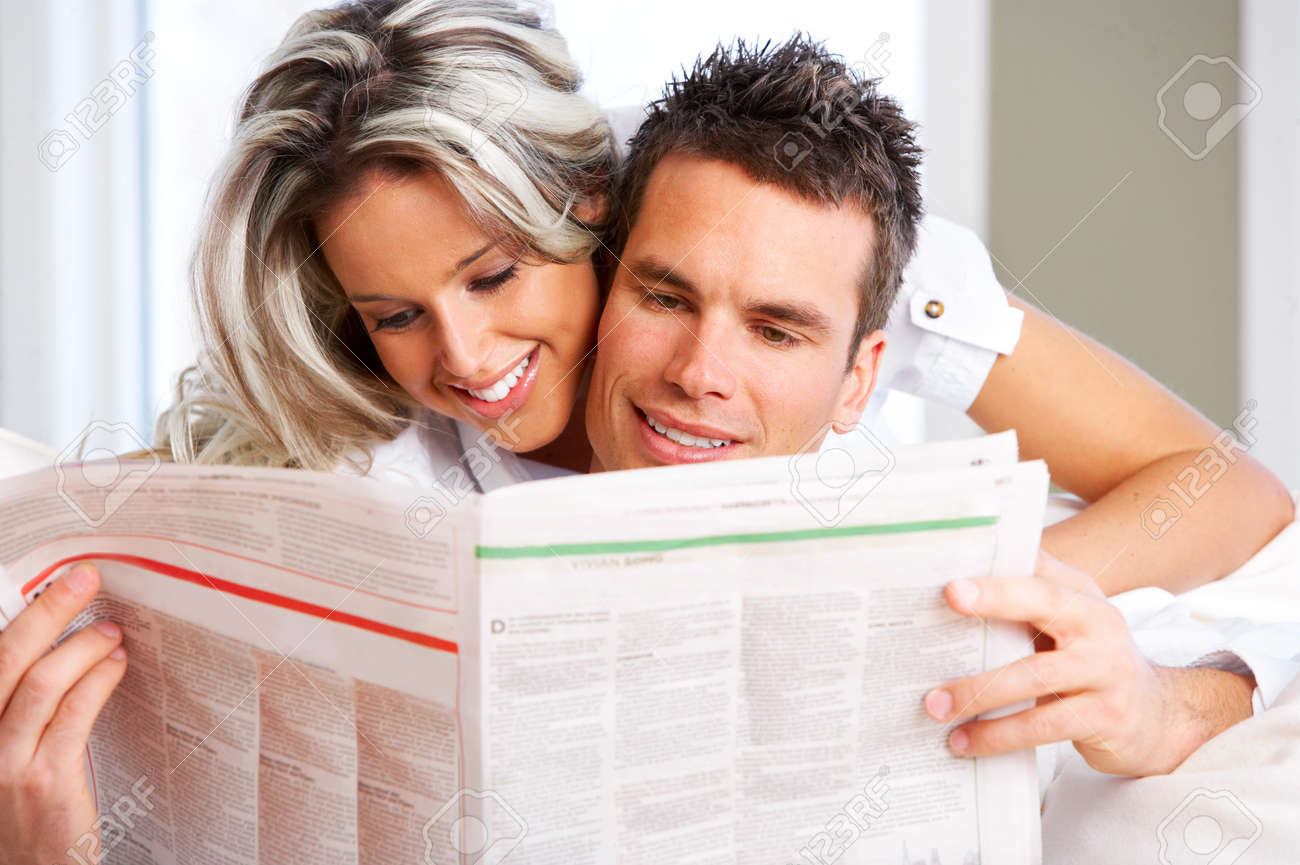 Young love couple reading magazine  in the comfortable apartment Stock Photo - 4108742