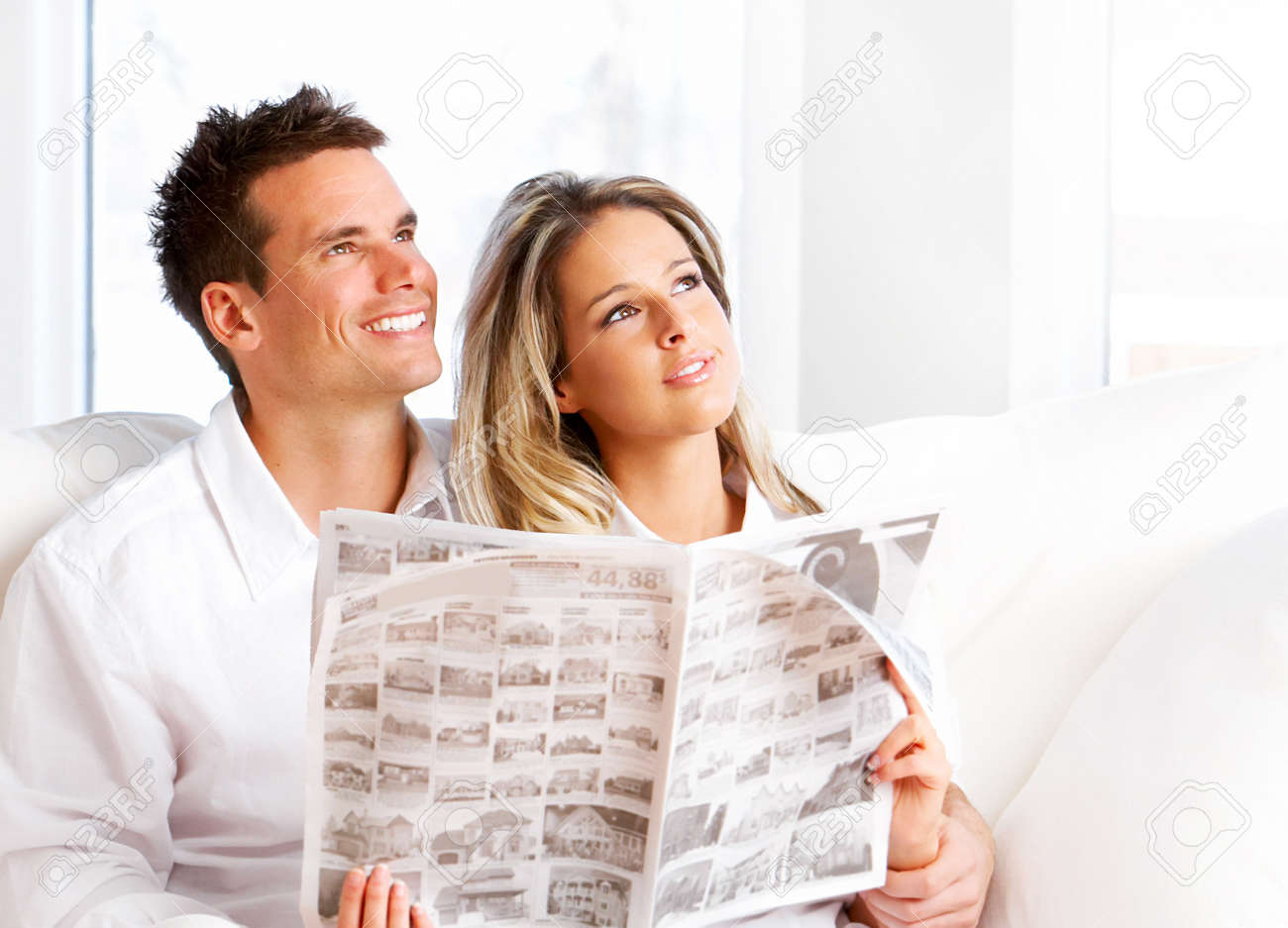 Young love couple reading magazine  in the comfortable apartment Stock Photo - 4420560