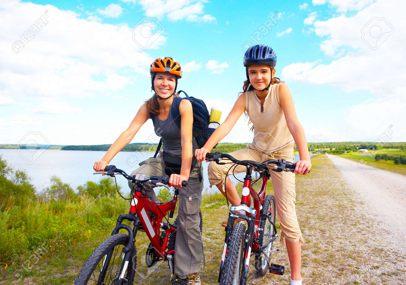 Mother and a daughter cycling near the lake - 4939463