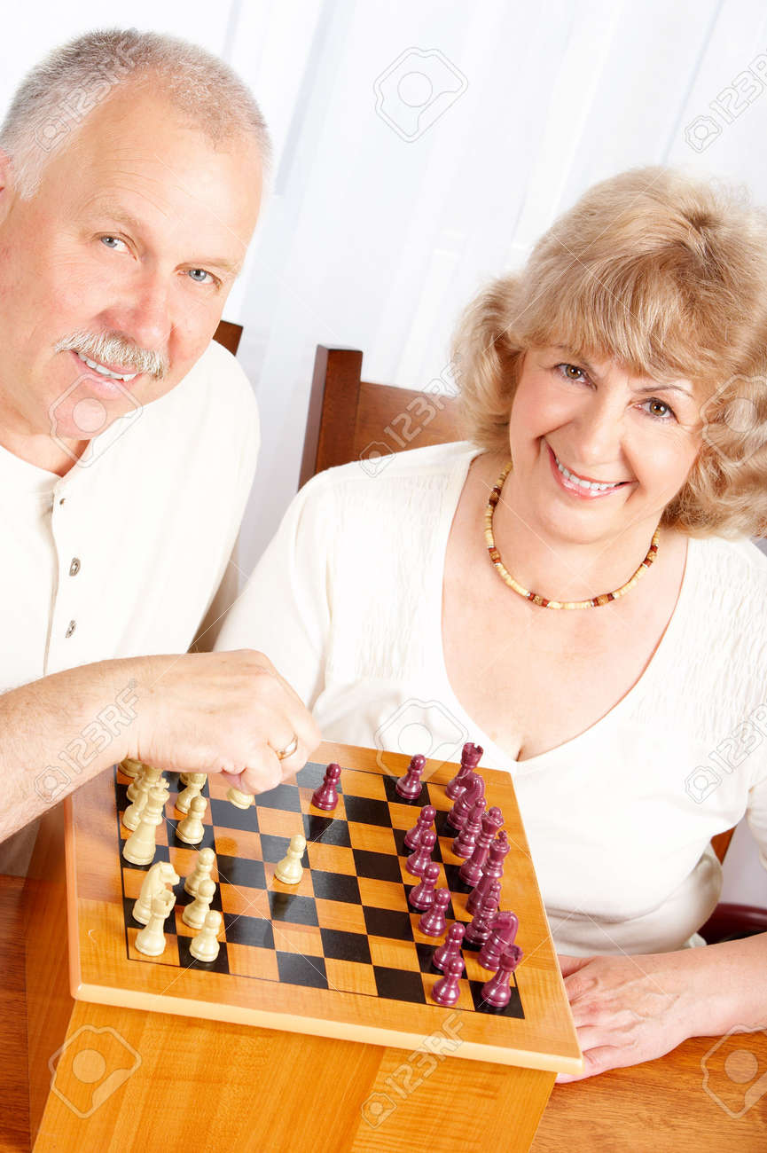 Happy smiling elderly couple playing chess at home Stock Photo - 5349757
