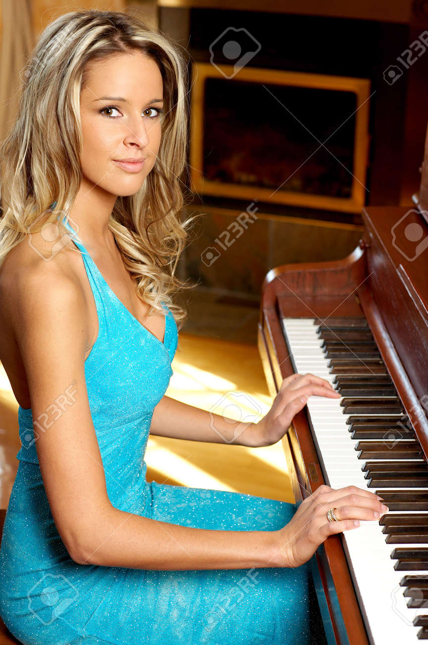Smiling  blonde woman playing the piano Stock Photo - 5493648