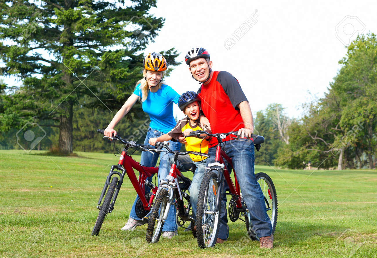 Happy family. Father, mother and son riding  in the park Stock Photo - 5487335