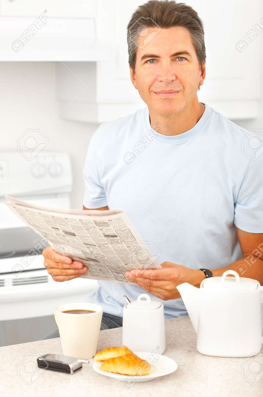 Young smiling man having lunch in  kitchen Stock Photo - 5525662